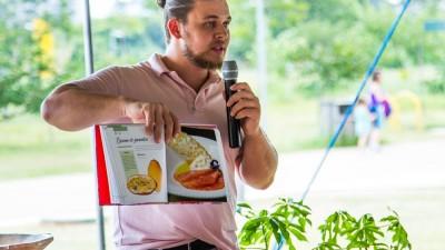 Chef Henrique Nunes, apresenta fotos em um livro ao público da Feira Viva.